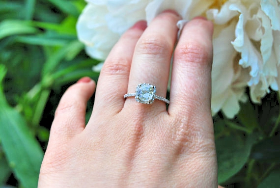white sapphire engagement rings in hand photos